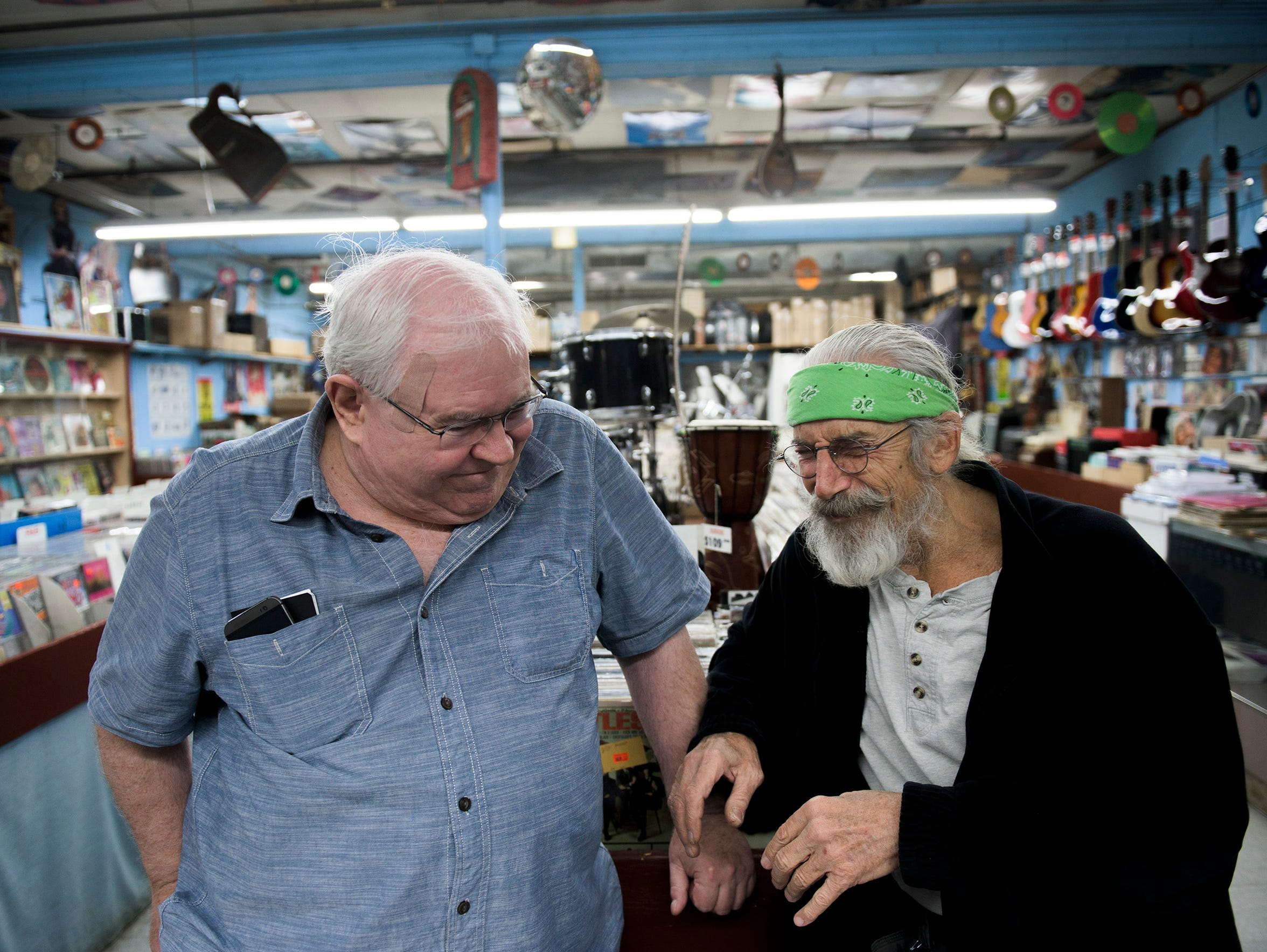 Owner Joe DiPietro, right, and long-time friend Bill Tracy share a laugh inside the Record Store at the Berlin Farmers Market. Tracy put together a photo book depicting the last few years inside the shop as a gift to his friend.