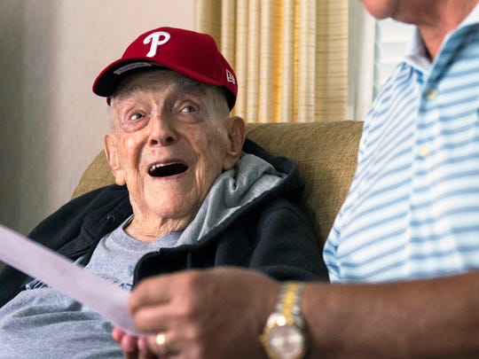 Retired Army Lt. Col. John 'Jake' Parvin, who recently turned 100, is surprised with a special game invite from the Philadelphia Phillies Tuesday, June 26, 2018 inside his home in Pennsauken, N.J.  His nephew David Yarnall of Washington Township read the baseball invitation to him. Inside a team tote bag the Phillies sent was the letter and a Phillies hat and jersey.