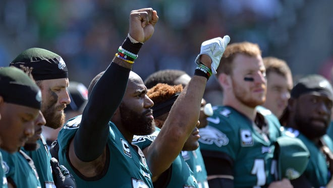 Philadelphia Eagles strong safety Malcolm Jenkins (middle left) and free safety Rodney McLeod (middle right) raise their fists during the national anthem as defensive end Chris Long (one from left) has his arm around Jenkins before the game against the Los Angeles Chargers at StubHub Center.