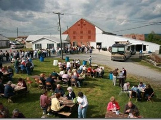Patrons line up to get into Singing in the Barn while others picnic and relax on the grounds.
