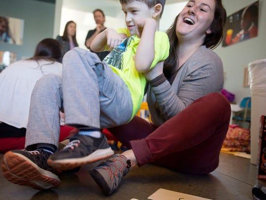 Behavior technician Megan Burton laughs and plays with