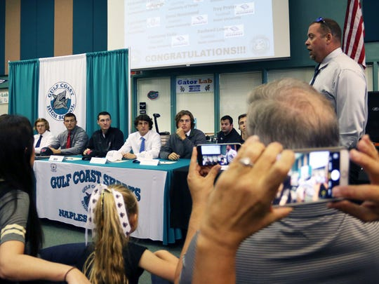 A room full of students, friends and family listen and take photos as Gulf Coast football coach Pete Fominaya speaks a during Gulf Coast High School's spring signing ceremony on Wednesday, April 12, 2017. The Sharks witnessed a record 14 student-athletes sign with collegiate programs during their spring ceremony.