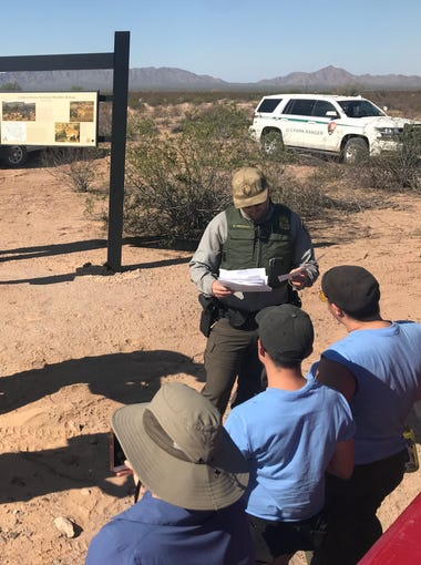 U.S. Park Rangers check the individual access permits for volunteers and clergy seeking to drop off water for migrants at Cabeza Prieta National Wildlife Refuge. Some volunteers have been cited in the past for dropping off water and accessing the area without a permit.
