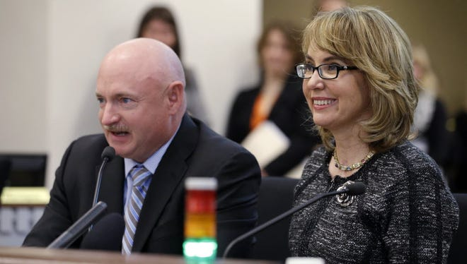 In this 2014 photo, former Arizona Rep. Gabrielle Giffords smiles as her husband, retired NASA space shuttle commander Mark Kelly, testifies before a Washington State House panel in Olympia, the capital.