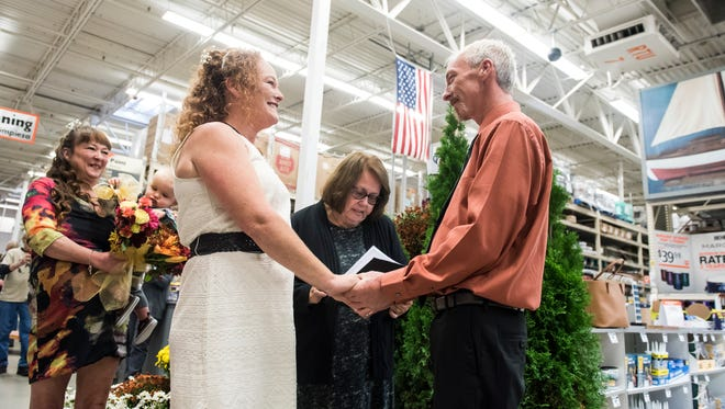 Rachel Dutterer and Daniel Lovell tie the knot in the paint section of the Hanover Home Depot on Friday, October 13, 2017.