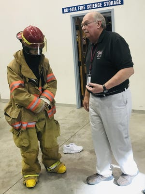 Boys and Girls Clubs of Pueblo County member Gemini M., left, receives advice on firefighting from Pueblo Community College fire science technology instructor John Webber.