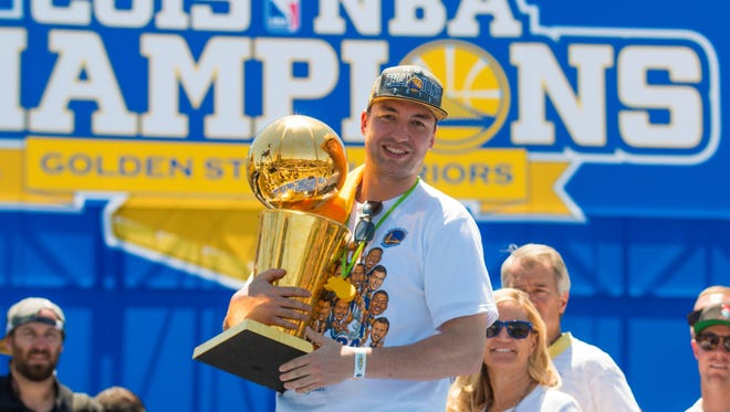 Xavier High School graduate Chris DeMarco celebrates the Golden State Warriors' NBA title by lifting the Larry O'Brien Championship Trophy during the team's postgame celebration.