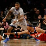 The Brooklyn Nets' Joe Johnson (7) and the Washington Wizards' Paul Pierce (34) dive for a loose ball during the second half of Saturday's game in New York. The Wizards won the game 99-90.