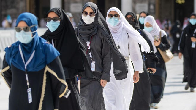 A picture taken on July 29, 2020 shows pilgrims circumambulating around the Kaaba, Islam's holiest shrine, at the center of the Grand Mosque in the holy city of Mecca, at the start of the annual Muslim Hajj pilgrimage. Mask-clad Muslim pilgrims began the annual hajj, dramatically downsized this year as the Saudi hosts strive to prevent a coronavirus outbreak during the five-day pilgrimage.