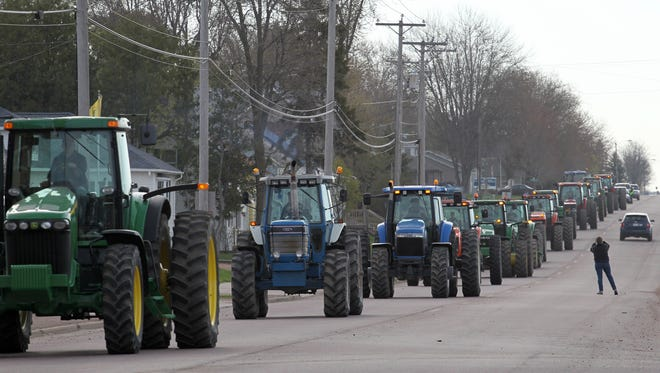 Tractors rumble down Main Street in Auburndale on Friday.
