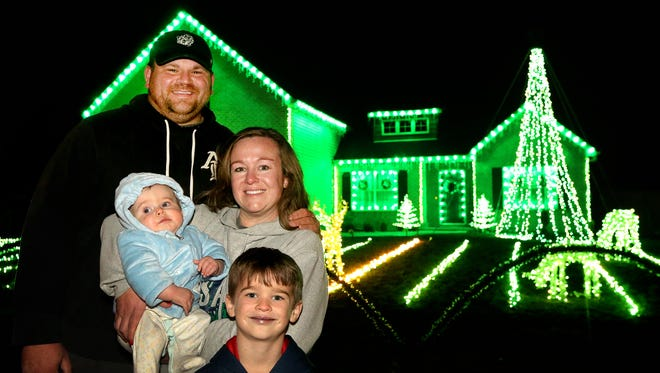 Aaron and Shannon Grimes stand in front of their Ridgeside neighborhood home with their children Tanner Grimes, 6, and 8-month-old Carson Grimes stand in front of the family's festive lights display in the Ridgeside subdivision off Barfield Crescent Road in Murfreesboro.
