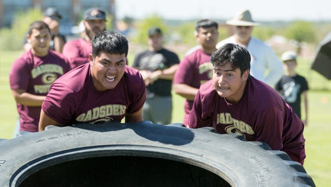 Gadsden High School football players Jonathan Jimenez, left, and Jesus Perez roll a tire on Saturday June 23, 2018, during New Mexico State University's 7 on 7 camp at the NMSU practice football fields.