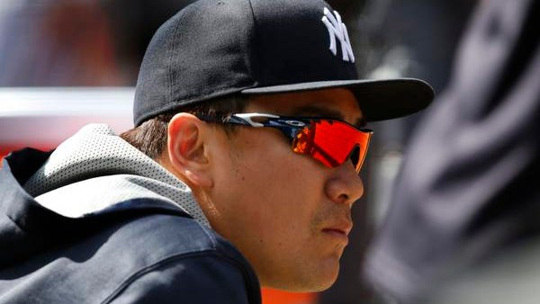 Yankees starting pitcher Masahiro Tanaka, who is on the 15-day disabled list with a forearm injury, watches from the dugout during a baseball game against the Tampa Bay Rays at Yankee Stadium in New York, Wednesday, April 29, 2015.