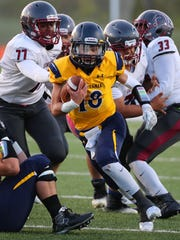 Whitnall quarterback Jacob Flores (18) keeps the ball for seven yards.