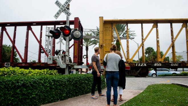 New York resident Alex Weber (left) and Cece Weber (center), of Stuart, wait to cross the Florida East Coast Railway tracks onto South Colorado Avenue in the area of Confusion Corner Dec. 26, 2014, when leaving downtown Stuart.