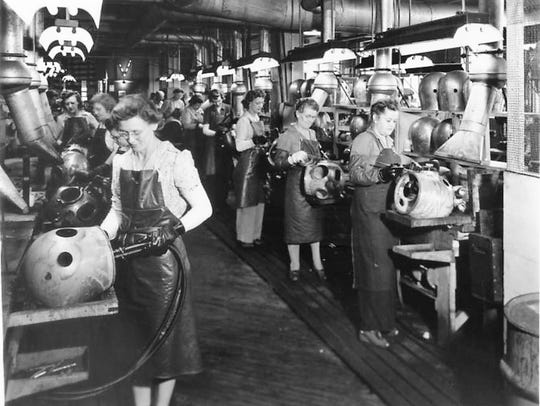 Female workers solder deep-water diving helmets at