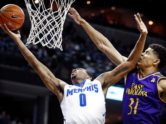 University of Memphis forward K.J. Lawson (left) drives past the defense of East Carolina University defender Andre Washington (right) for a layup during second half action at the FedExForum. Lawson finished the game with a career-high 19 rebounds while adding12 points.