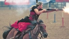 A competitor in a rifle class shoots at balloons during a sport called cowboy mounted shooting.