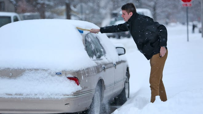 """Butler student Kirby Lawson reaches to start cleaning off his car, on Hampton Dr., after an overnight snowfall, Tuesday, January 6, 2015.  He is originally from Chicago and had recently spent two hours defrosting his car because his doors were frozen shut.  """"So here in Indianapolis, I'd take the snow over the cold any day,"""" he said."""