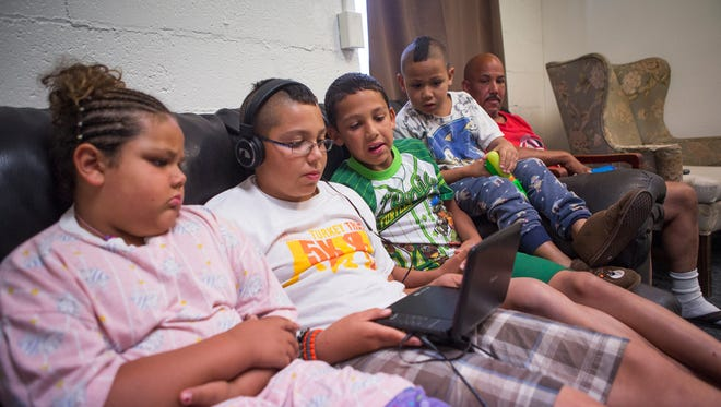 """John Nettles, right, looks on as his children watch a show together on a portable DVD player in the play room at The Valley Mission on Aug. 8, 2015. """"I wanted to try and make my kids feel at home,"""" said Nettles, describing how he brought a TV into the shelter but had to take it out of their room due to one of the organization's policies. """"There's a lot of things that you can't have, but I still try anyway."""""""