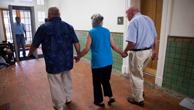From left to right, Julian Parrott's uncle, Daniel Peyton, and grandparents, Suzanne Fulton and Jack Fulton, walk hand in hand out of the Cochran Judicial Center during a break from the murder trial of 17-year-old Isaiah Stuart, who stands accused of killing Parrott, on Friday, Aug. 28, 2015.