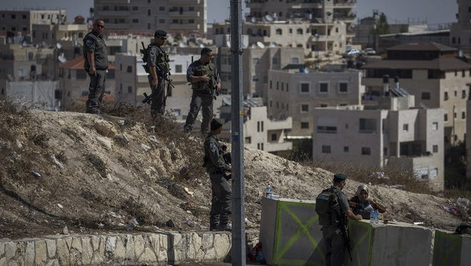 Palestinians pass a checkpoint in Issawia neighbourhood on October 16, in Jerusalem, Israel.