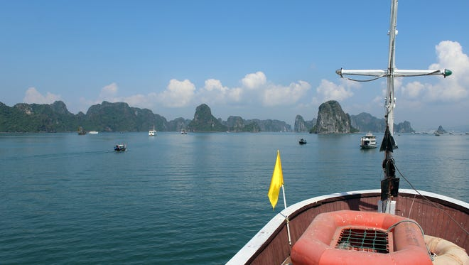 Boats of all sizes cruise calm Ha Long Bay.
