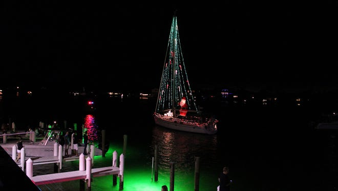 One of the boats passes the prime viewing spot at the Snook Inn during the annual Christmas Island Style parade.