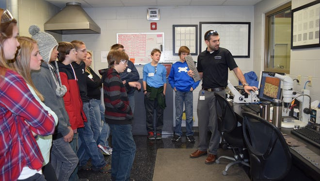 Kondex metallurgical engineer Casey Placek explains how Kondex products are metallurgically examined to middle school students from Kewaskum.