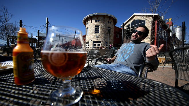 Kyle Huffman talks to a friend over beers on the patio at Odell Brewing.
