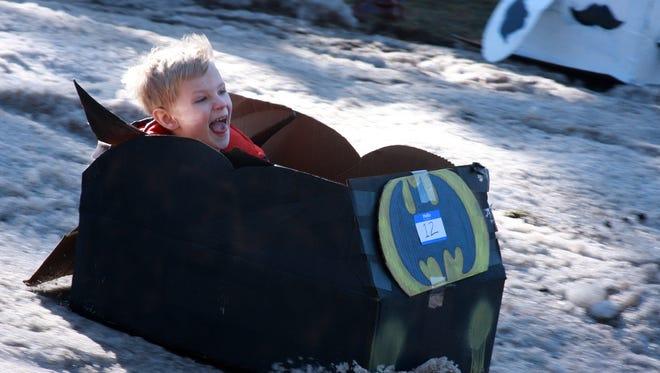 Jackson Hacker, 5, enjoys his cardboard sled ride during Festivas Saturday afternoon