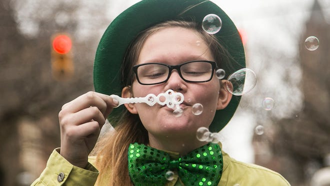 Adrianna Pinto, 14, of Mount Rose, blows bubbles as she waits for the St. Patrick's Day Parade to start Saturday, March 12, 2016. Amanda J. Cain photo