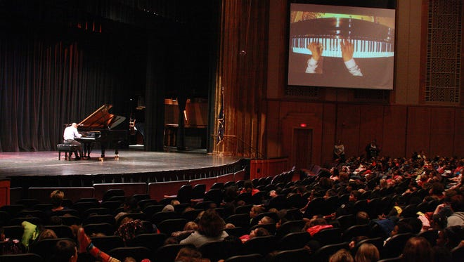 Pianist Terrence Wilson had a camera placed above the keyboard. It was projected on large screens so the students from Battle Creek Elementary schools could watch his fingers move quickly over the keyboard Wednesday morning at W.K. Kellogg Auditorium.