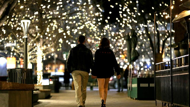 Kiarra McDowell and Seth Lanier hold hands as they share a romantic walk through Old Town Square on Valentines Day in Fort Collins, Colo.
