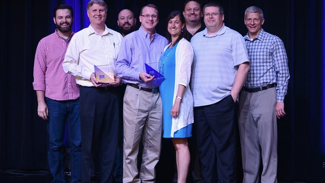 Staff of Interactive Dynamics pose after accepting the award Wednesday.