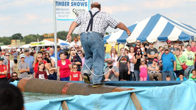 Bruce Belanger, 62, jumps rope on the rolling log for spectators at The Great Lakes Timber Show Thursday evening.