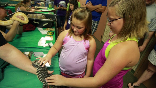 Khloe Carptenter, 7, and her sister Kaylee, 11, touch an Argentine Black and White Tegu Sunday at Battle Creek's Binder Park Zoo as a part of Reptile Weekend.