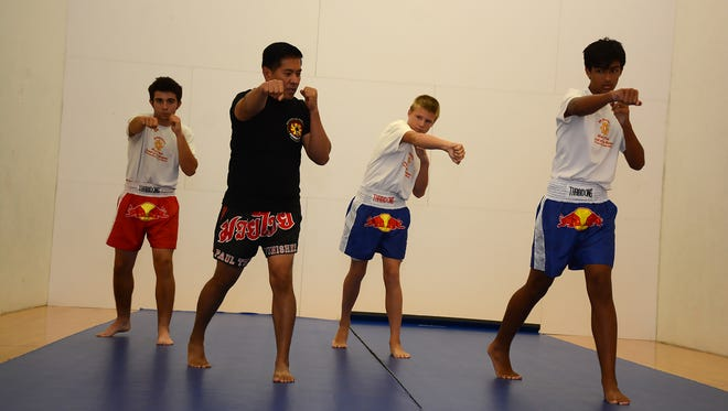 Instructor Paul Rosales, in black, leads students in practicing strikes. City-sponsored martial arts classes are being held in the Marco Island Racquet Center during the month of August.