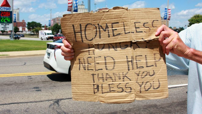 A panhandler stands on the corner of Capital Avenue Southwest and East Dickman Road.