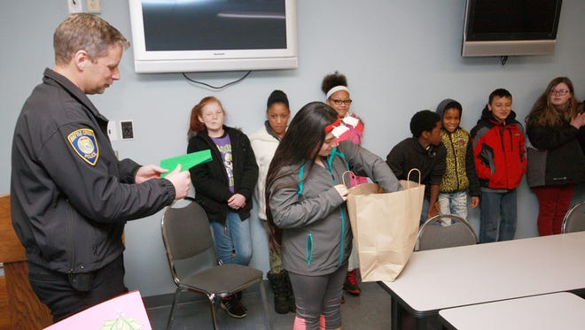 Jessica Perez gives out a few of the holiday cards that Springfield Middle School sixth, seventh and eighth graders made for the Battle Creek Police Department in their teen leadership class.