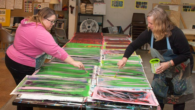 Kimber Thompson, left, and Sabine LeDieu use old political signs that have been donated to create their signs of hope.