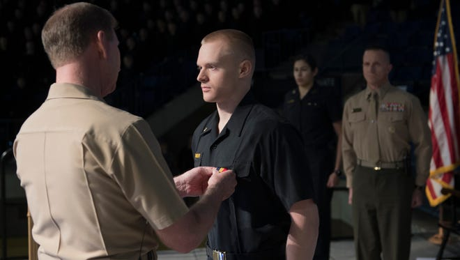 U.S. Naval Academy Superintendent Vice Adm. Ted Carter pins the Navy and Marine Corps Medal for heroism on Midshipman 3rd Class Jonathan Dennler of Medford, who canoed in a thunderstorm for help after two people on a Boy Scout camping trip were killed and others injured in Canada last summer.