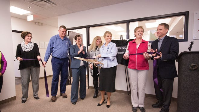 Dignitaries from Denso Manufacturing Michigan Inc. including President Andris Staltmanis, far right, and retired Vice President Karen Cooper-Boyer, middle with the scissors, cut the ribbon Thursday at the new Denso Family Health Center in Battle Creek.