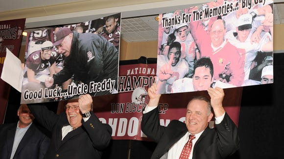 Former Bergen Catholic High School football coach and competitive rival Fred Stengel (left) and Don Bosco Prep head football coach Greg Toal show a poster gift from each other at a Roast and Toast dinner for Toal after Don Bosco won the 2009 national high school football championship.