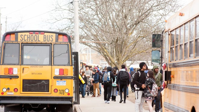 Kids get on the buses or head to their cars to leave Battle Creek Central High School at the end of the school day.