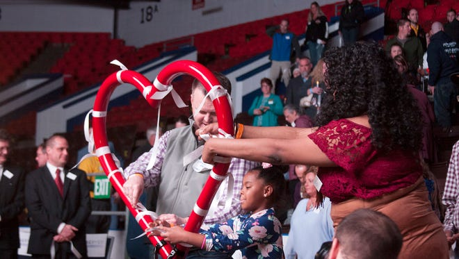 Community members tie ribbons on the infinity heart that is now the logo for ForeverStrong at a memorial service for the victims of the Kalamazoo mass shooting at the Wings Event Center on Monday evening.