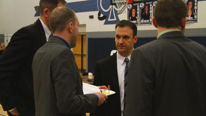 Granville coach Adam Teeters confers with his staff during a win against Watkins Memorial. Teeters led the Blue Aces to a second consecutive LCL Buckeye Division title.
