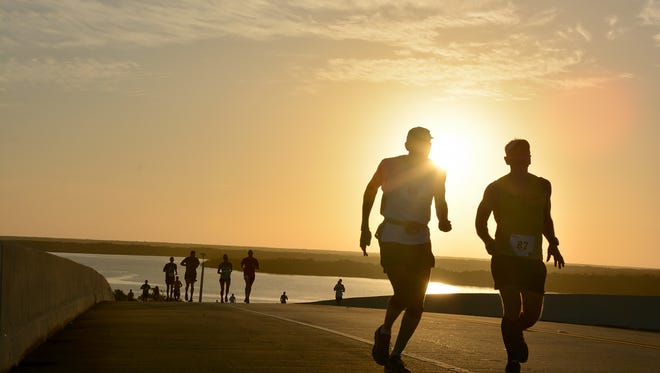 File: Runners cross the Stan Gober Memorial Bridge as the sun rises during the Marco Island Half Marathon and 5K.
