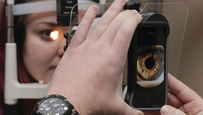 Kristopher Skromme, owner of Two Trees Optometry, uses a mobile phone camera to take pictures of the eye during an exam.