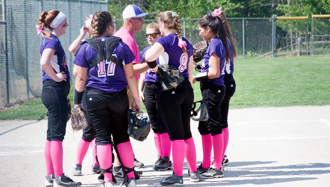 Lakeview softball huddles up before the start of their Swing Pink game against Loy Norrix Tuesday evening.